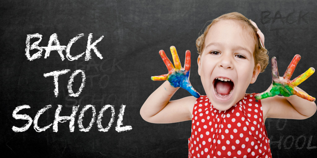 Positive child with colorful hands by sign back to school